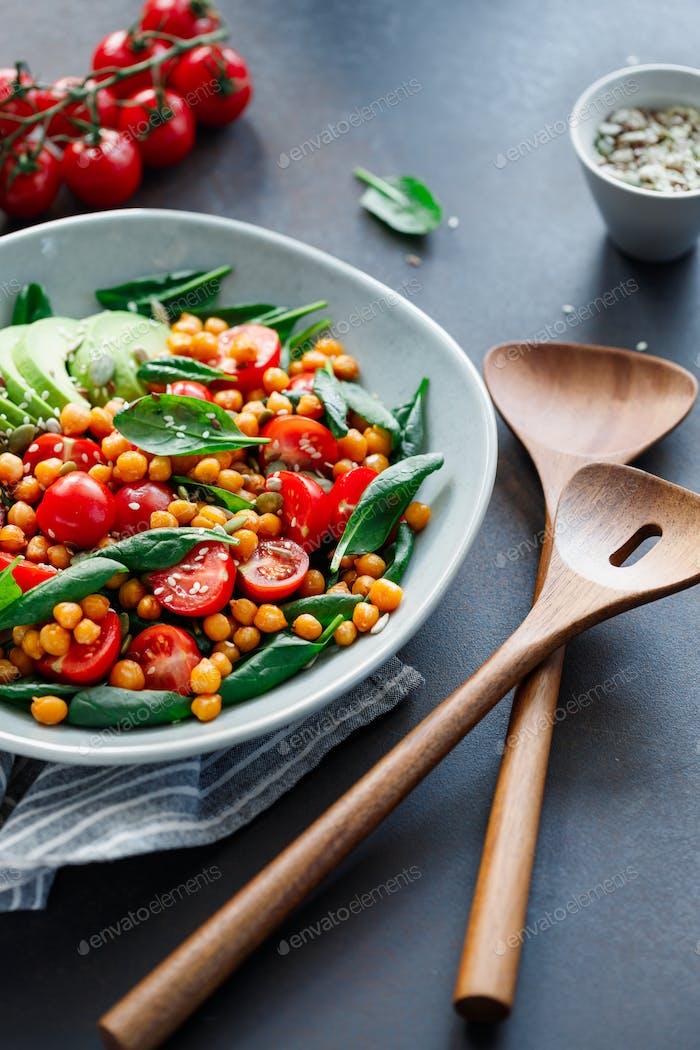 Frischer gesunder Salat mit Kichererbsen, Avocado, Kirschtomaten und Spinat.