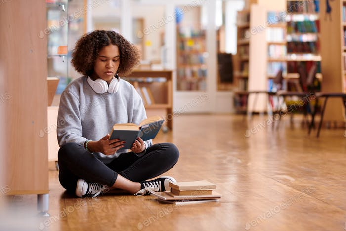 Contemporary girl in skinny jeans and grey sweatshirt reading book