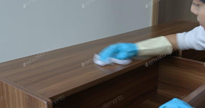 Mujer limpiar el gabinete de televisión en casa