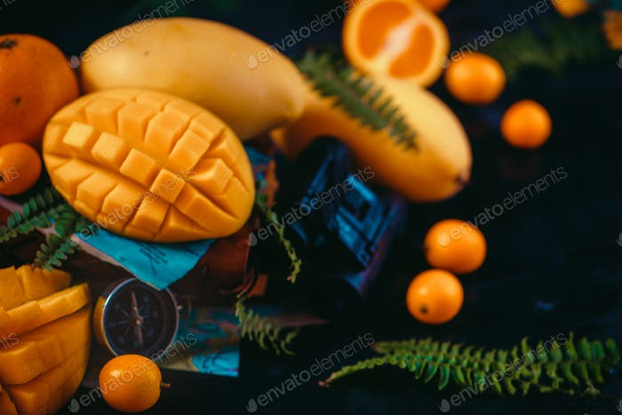 Cut mango halves close-up header with oranges, kumquat, and other tropical fruits. Dark background