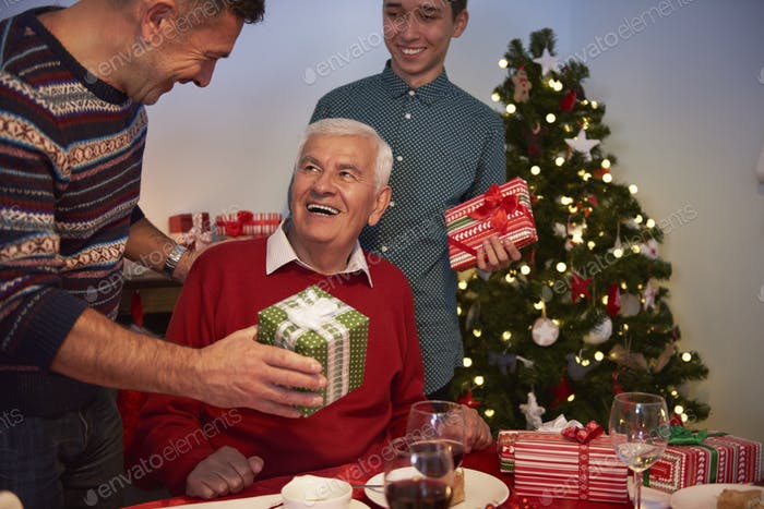 Very happy grandfather receiving Christmas presents