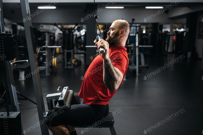 Athlete in sportswear on exercise machine in gym