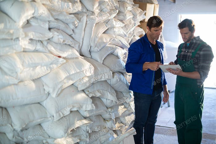 Coworkers discussing while standing barley sacks