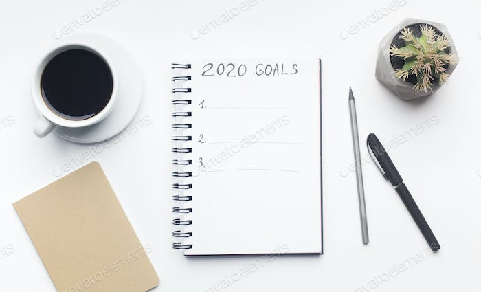 Goals list in notepad with pen and cup of coffee on white