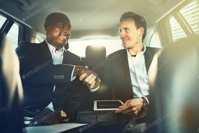 Empresarios estrechando la mano juntos en el asiento trasero de un coche