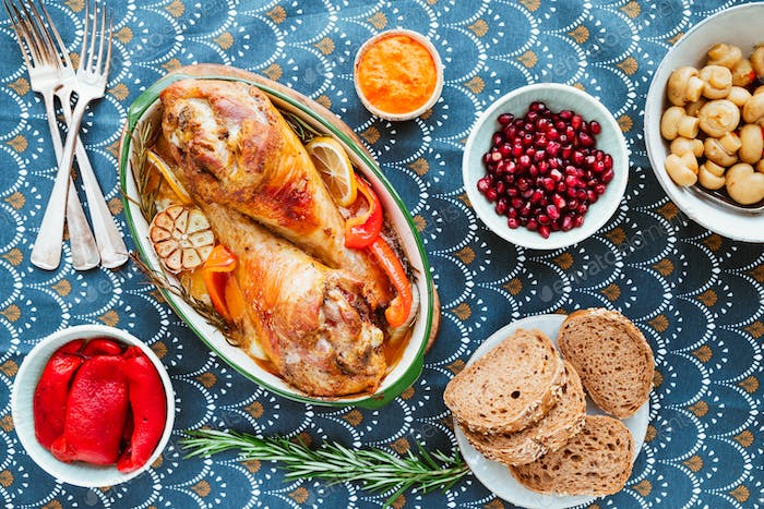 Festive dish for Thanksgiving, roasted turkey legs with vegetables on a table with snacks