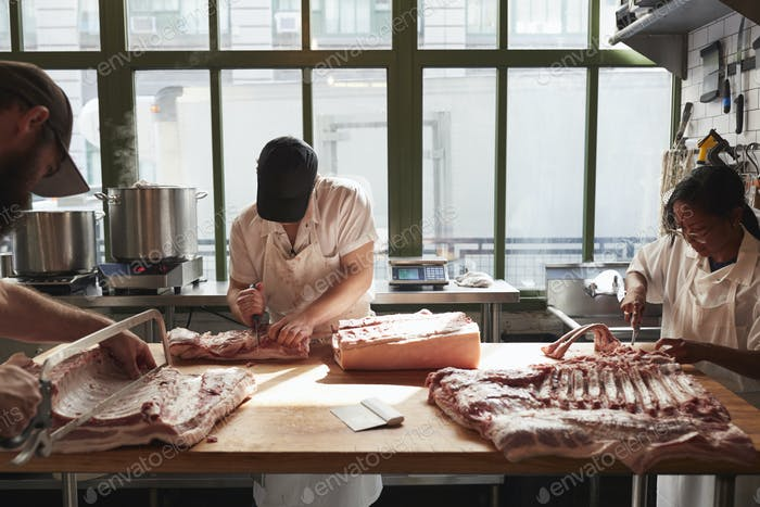 Three butchers preparing pork at a butcher's shop