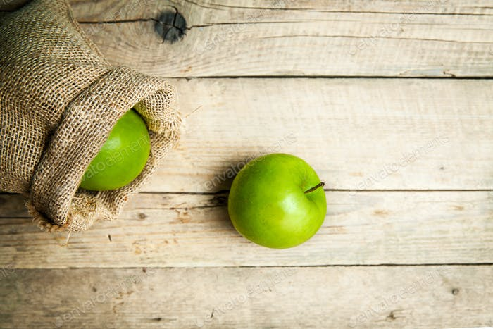 fruit. Ripe green apples with burlap, on wooden background