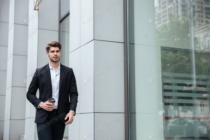 Businessman walking and drinking take away coffee in the city