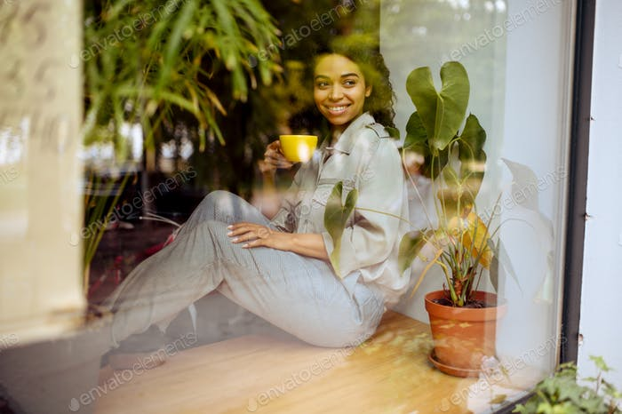 Student with coffee sitting on windowsill in cafe
