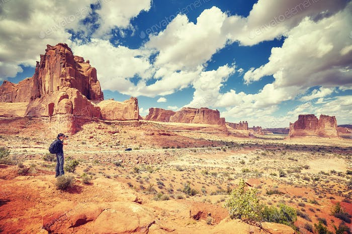 Female photographer takes pictures in Arches National Park.