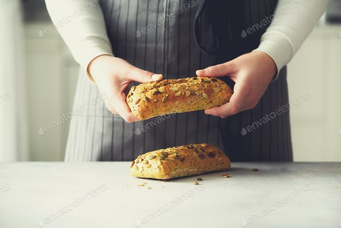 Woman hands holding freshly baked bread. Bun, cookie, bakery concept, homemade food, healthy eating