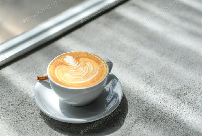Coffee heart latte on a concrete floor with natural light by the window.