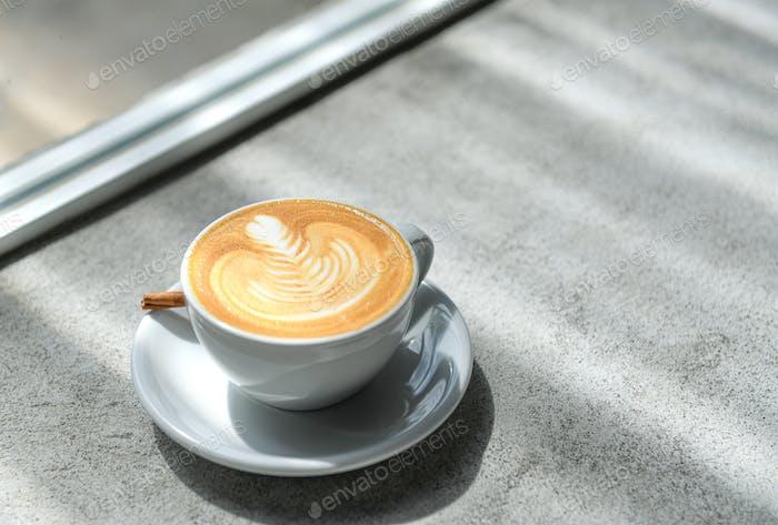 Kaffee-Herz Latte auf einem Betonboden mit natürlichem Licht am Fenster.
