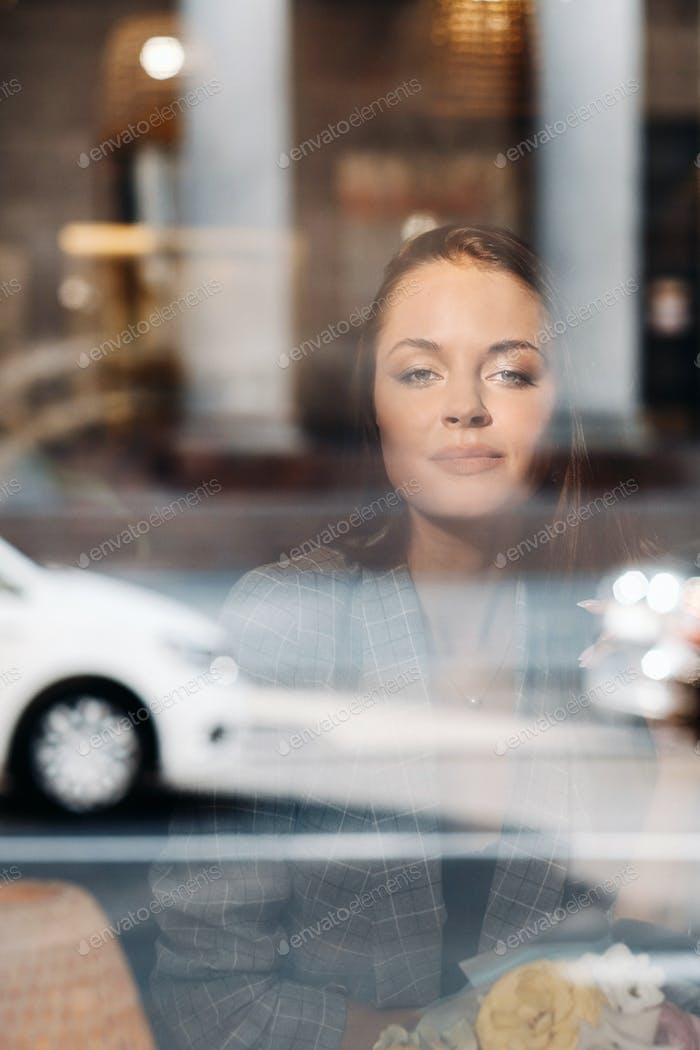 Retrato de una joven europea con el pelo largo en un café sentado cerca de la ventana, una chica alta en un
