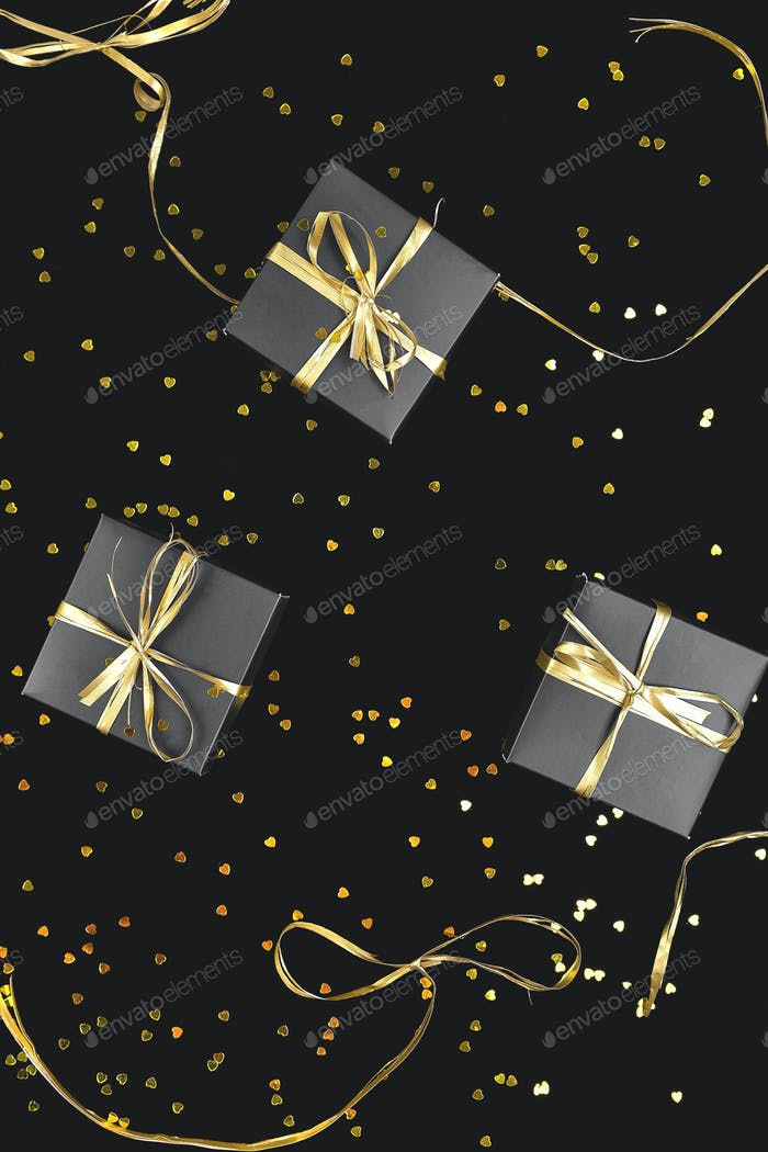 Black gift boxes with gold ribbon on shine background.