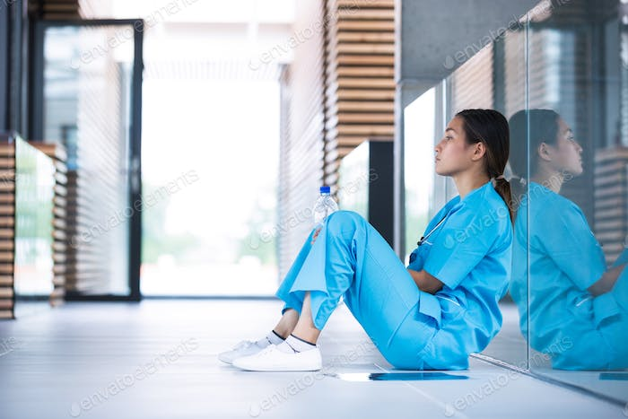 Depressed nurse sitting on floor