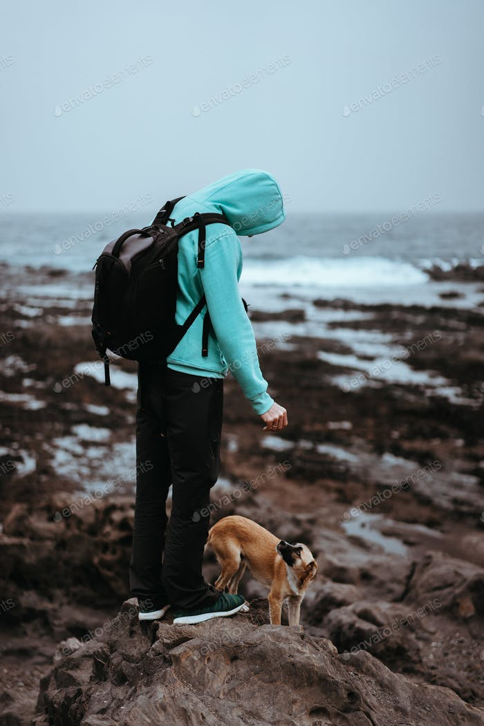 Man with a dog on stony coastline of Santo Antao Island, Cape Verde