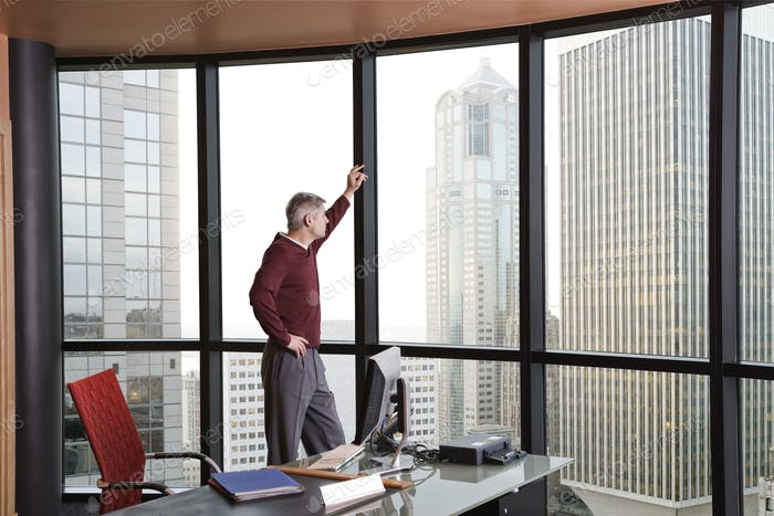 Casually dressed caucasian businessman standing and looking at a skyline out an office window.