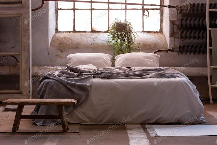Echtes Foto von einem Wabi Sabi Schlafzimmer Interieur mit einem Bett, Pflanze und