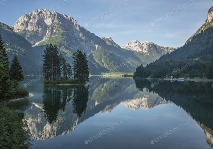 Beautiful forest reflection at the Predil lake with surrounding mountains