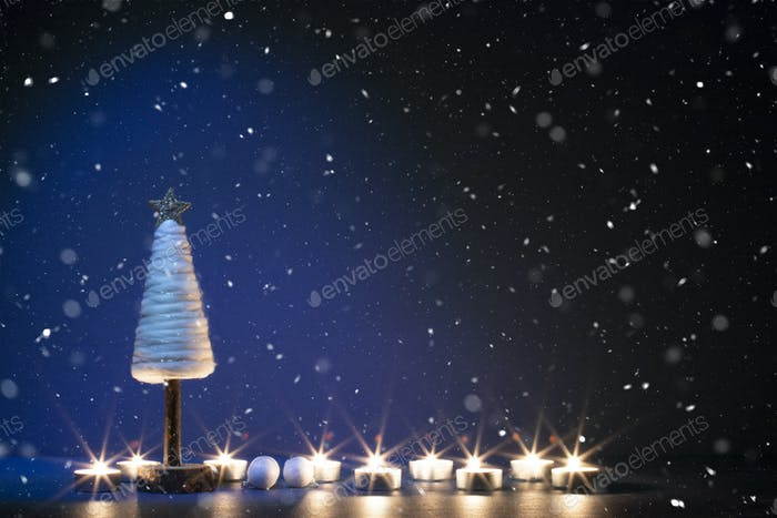 Christmas tree with candles in snowfall.