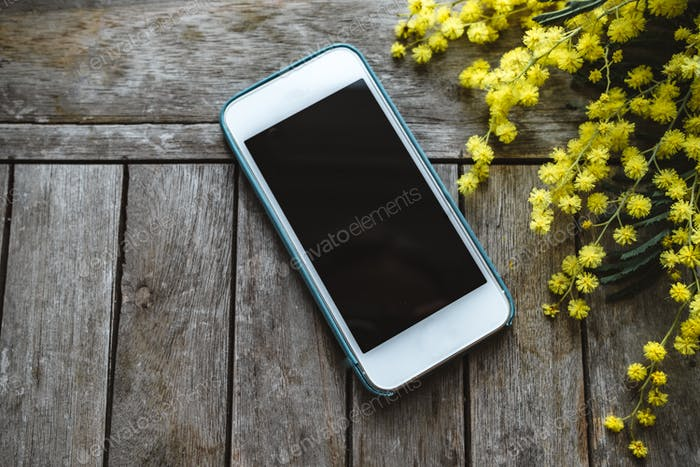Phone on a wooden table with mimosa. Top view
