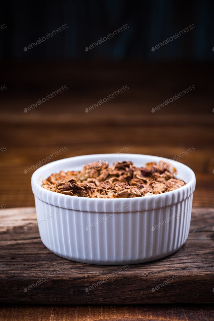 Baked apple with oats and crunch in ceramic pot