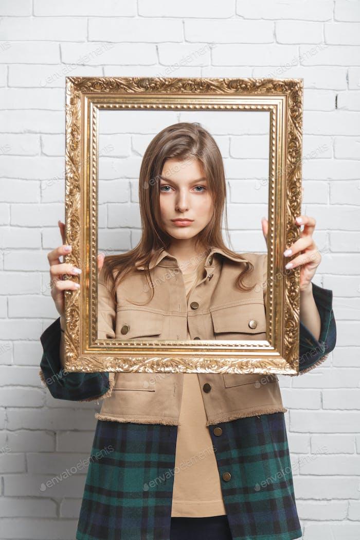 Junge Frau hält den Rahmen vor ihr. Grenz- und Stereotypenkonzept