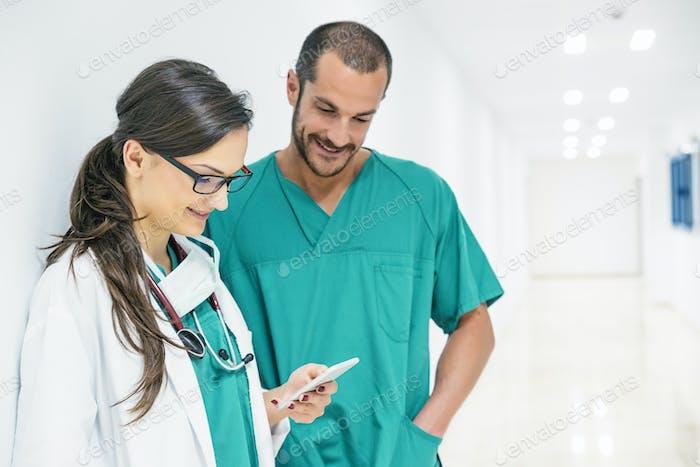 Médico y enfermera usando el móvil.