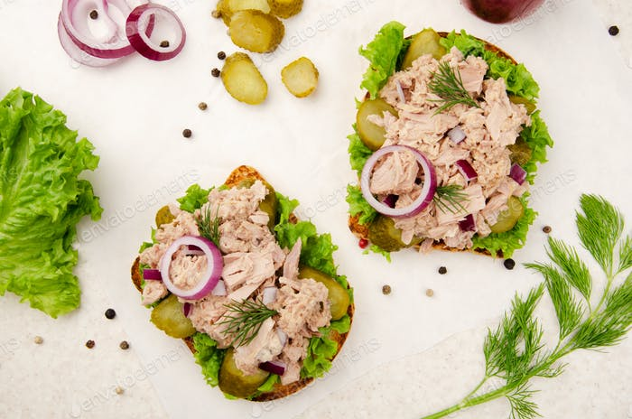 Flat lay view at Tuna sandwiches with lettuce tomatoes pickles and onions on parchment paper