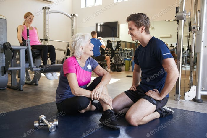 Senior Woman Discussing Exercise Program With Male Personal Trainer In Gym