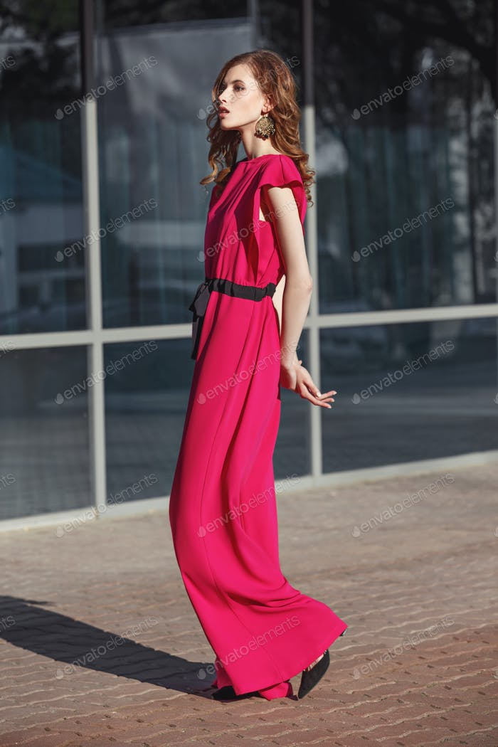 Slim stylish brunette girl dressed in fuchsia color overalls is walking in the city street on a