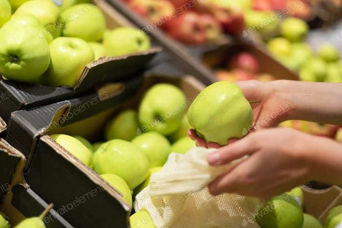 Woman chooses green apples at farmers market. Zero waste, plastic free concept. Sustainable