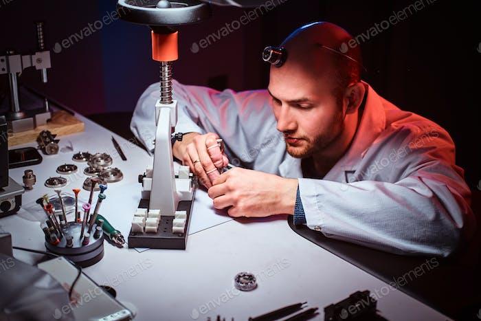 Der  reife Uhrmacher arbeitet in seinem eigenen Atelier.