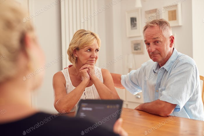 Retired Couple Meeting With Female Financial Advisor In Kitchen At Home