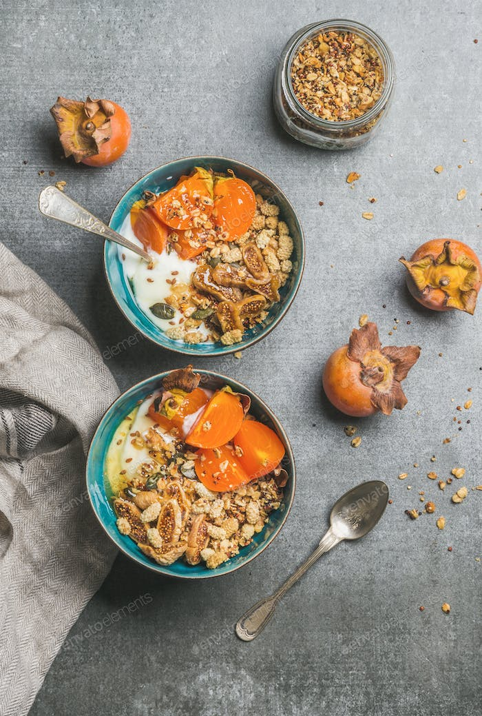 Oatmeal, quinoa granola, yogurt, seeds, honey, persimmon in blue bowls