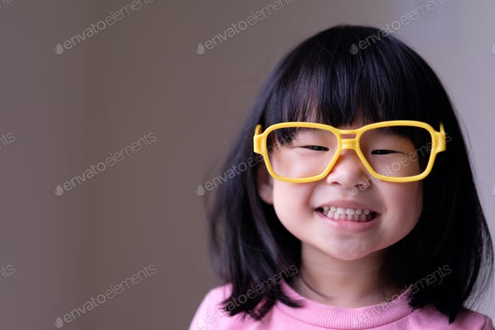 Funny little child with big yellow glasses