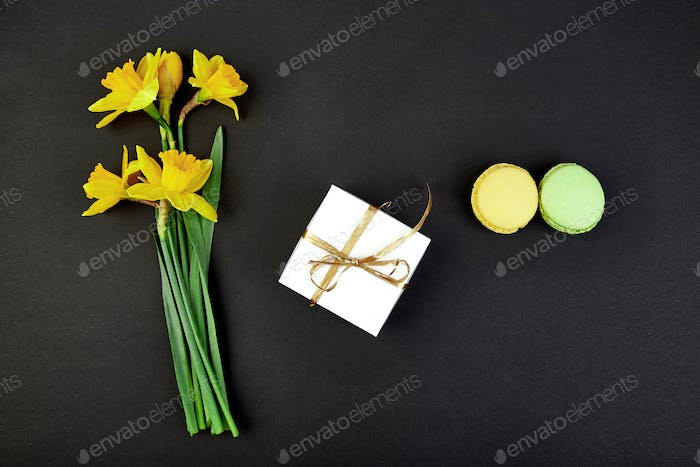 Bouquet flowers narcissus gift and sweets or cake macarons.
