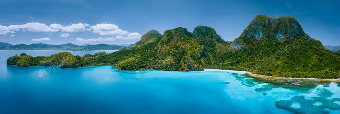 Aerial drone panoramic view of uninhabited tropical island with rugged mountains, rainforest jungle