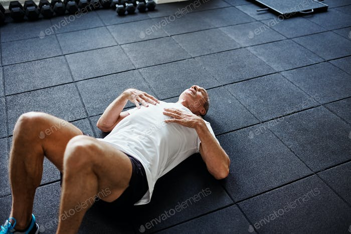Exhausted man lying on a gym floor after working out