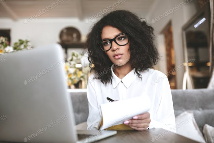 Young lady with dark curly hair sitting at cafe with notebook in hand
