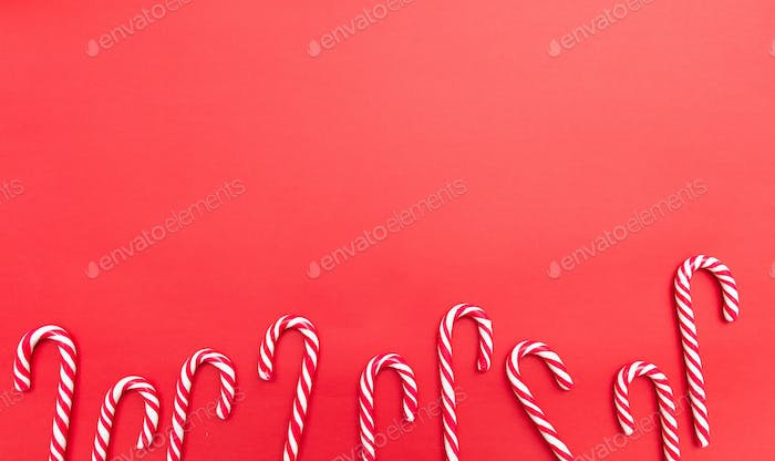 Candy canes on red background, copy space