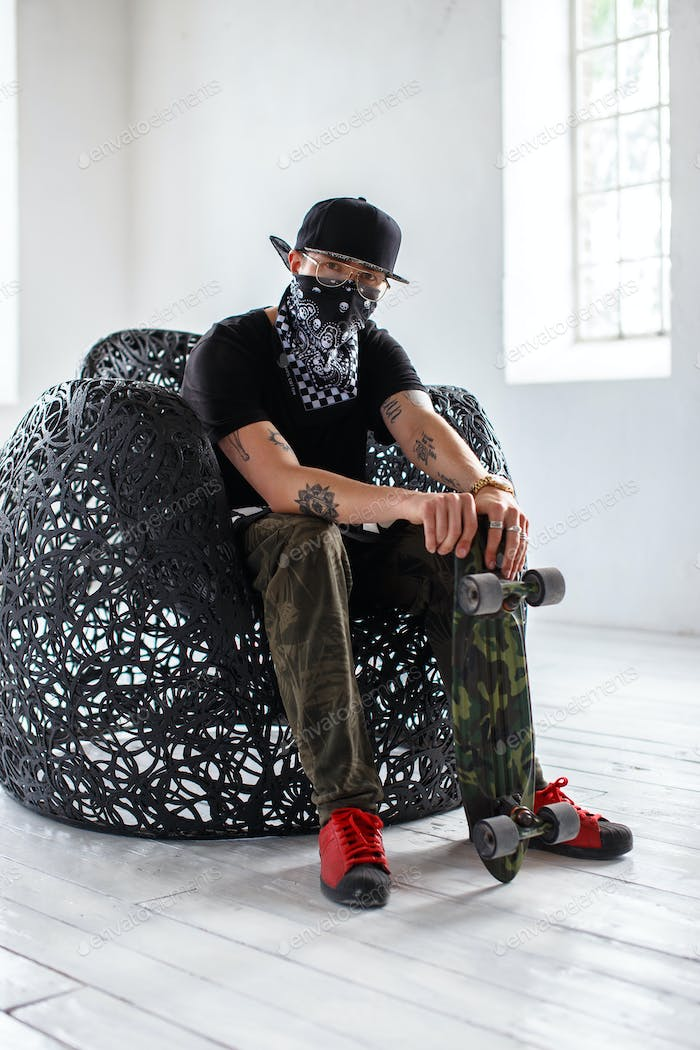 A man in a mask sits on a chair and holds skateboard.