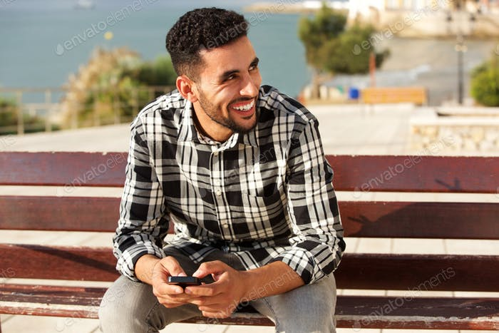 young arabic man smiling outside with mobile phone