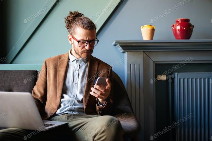Genieße seine Arbeit. Glückliche junge erfolgreiche Geschäftsmann im Gespräch auf dem Handy