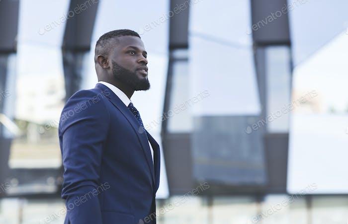 Серьезный черный бизнесмен, глядя в сторону стоя в городской местности