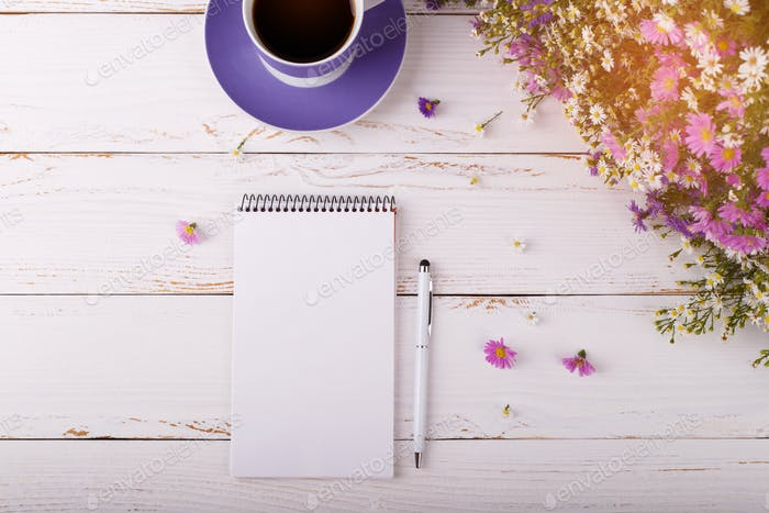 Notepad with pen coffee and flowers