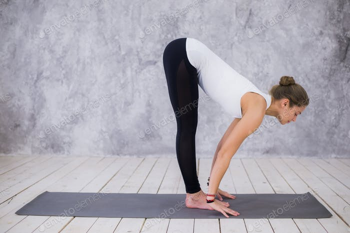 Beautiful young woman working out indoors, doing yoga exercise in the room with white walls