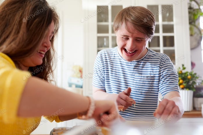 Young Downs Syndrome Couple Baking Cupcakes In Kitchen At Home